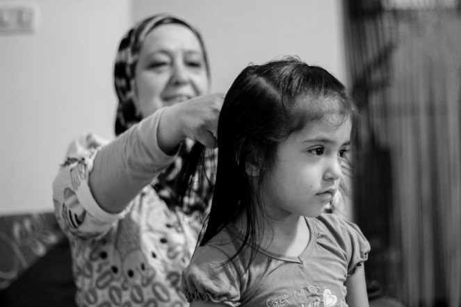 Arwa Sabony, The manager of the association for the Syrian women in Tenth of Ramadan while she was hairdressing her granddaughter Julia
