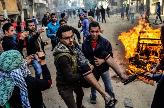 gyptians carry an injured protester during clashes between supporters of the Muslim Brotherhood, local residents and security forces in Giza, near Cairo, Egypt, 24 January 2014