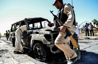 Egyptian soldiers inspect a burnt out car at the site of car bomb attack, in al-Tor, South Sinai, Egypt, 07 October 2013. Ten people were killed on 07 October in a bombing of the security headquarters of Egypt's South Sinai province and an ambush of soldiers near the Suez Canal city of Ismailiya, security officials said. Five people died in the car bombing, which occurred as senior officials were holding a meeting. At least 50 people were reported injured in the blast in al-Tor, the provincial capital.
