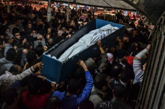 Egyptian mourners carry the coffin of Sayed Abdallah, a member of the 6 of April movement who was killed in clashes a day earlier, during his funeral in Cairo, Egypt, 26 January 2014