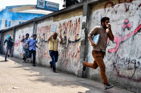 CAIRO, EGYPT - APRIL 16: Egyptian students run for cover from tear gas fired by security forces during the anti-coup protests at the Al-Azhar University on April 16, 2014 in Cairo, Egypt.