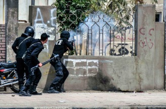 CAIRO, EGYPT - APRIL 16: Egyptian security forces fire tear gas to disperse anti-coup students during a protest at the Al-Azhar University on April 16, 2014 in Cairo, Egypt.