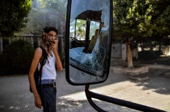 A student of Al-Azhar University looks on while standing next to a broken mirror of a smashed bus that was damaged during clashes between students and security forces, in Cairo, Egypt, 20 October 2013. A group of Al-Azhar University students protested against the ousting of Islamist president Mohamed Morsi in July and called for the dismissal of Al-Azhar Grand Imam Ahmed El-Tayeb. Security forces and students clashed after students tried to march to the nearby Rabaa Adawiya mosque, the former site of pro-Morsi sit-in.